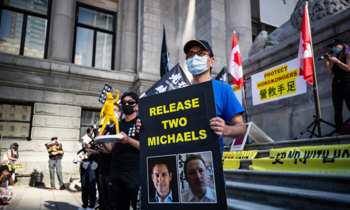 A man holds a sign with images of Michael Kovrig and Michael Spavor who have been detained in China since December 2018, as people gather for a rally in support of Hong Kong democracy, in Vancouver on Aug. 16, 2020. (Darryl Dyck/The Canadian Press)