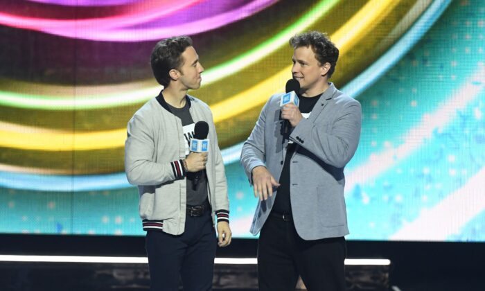 Co-founders of WE Charity co-founders Craig (L) and Marc Kielburger speak on stage during WE Day California at the Forum in Inglewood, Calif., on April 25, 2019. (Valerie Macon/AFP via Getty Images)