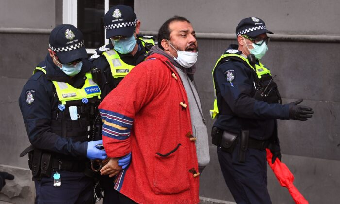 Police detain a protester at a small-scale rally against COVID-19 restrictions in Melbourne on Aug. 9, 2020. (William West via Getty Images)