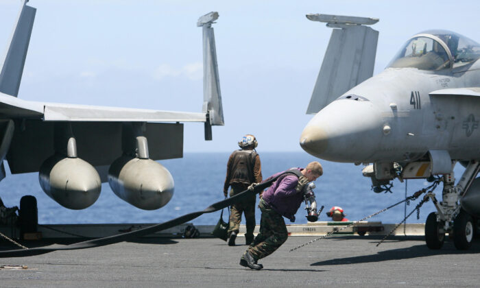 A US Navy crewman pulls a fuel pipe across the deck of USS Kitty Hawk (CV63) aircraft carrier in the Bay of Bengal, during the Malabar exercise on Sep. 7, 2007.   (Deshkalyan Chowdhury/AFP via Getty Images)