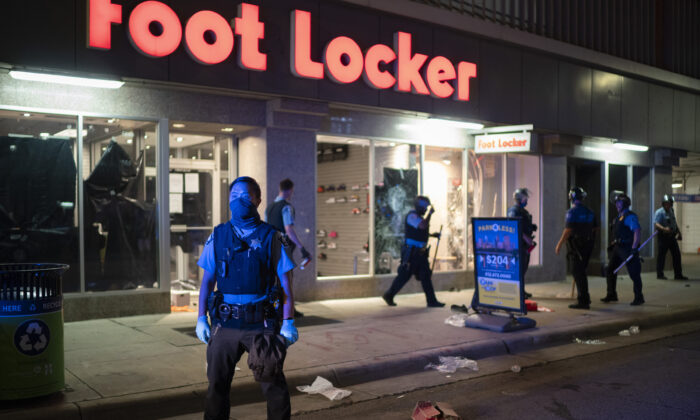 Minneapolis Police stand outside a looted Foot Locker store on S. 7th St. in Minneapolis on Aug. 26, 2020. (Jeff Wheeler/Star Tribune via AP)