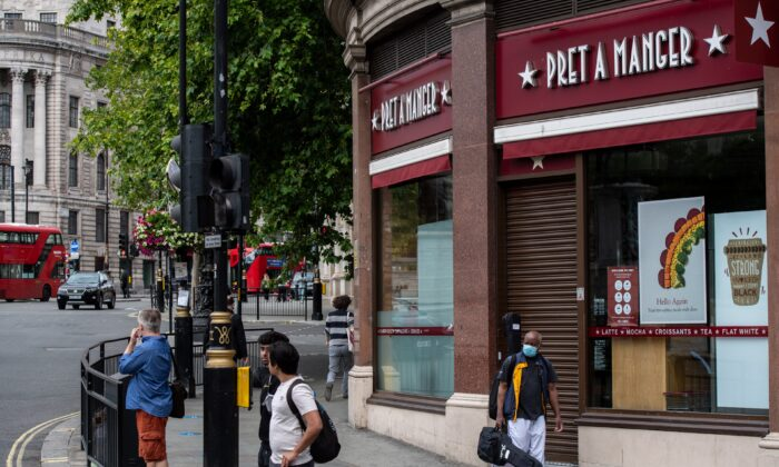 A musician wearing a face mask walks past a currently closed Pret a Manger restaurant in Trafalgar Square, London, on July 6, 2020. (Chris J Ratcliffe/Getty Images)