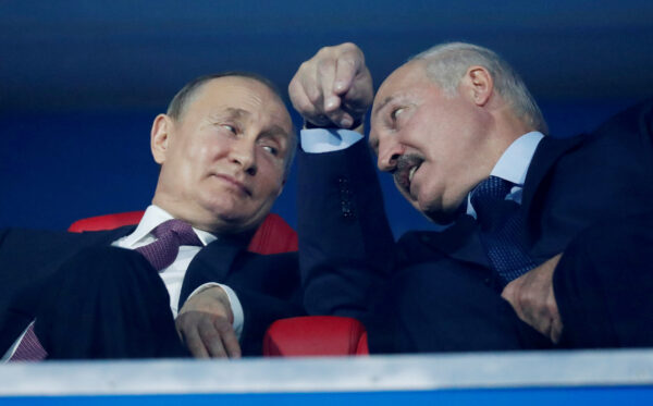Vladimir Putin and Alexander Lukashenko speak in the stands during the closing ceremony in Dinamo Stadium