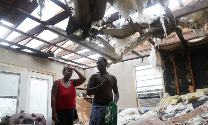 Latasha Myles and Howard Anderson stand in their living room where they were sitting when the roof blew off around 2:30 a.m. as Hurricane Laura passed through the area in Lake Charles, La., on Aug. 27, 2020. (Joe Raedle/Getty Images)
