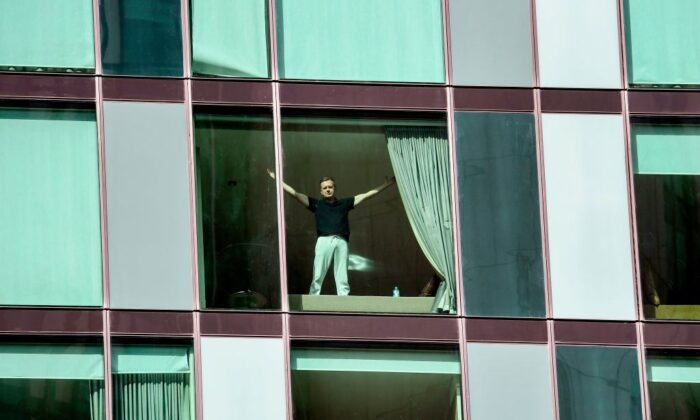 A man gestures to the cameras in an inner-city hotel where travellers returned from overseas are staying in isolation in Melbourne on March 30, 2020. (William West/AFP via Getty Images)