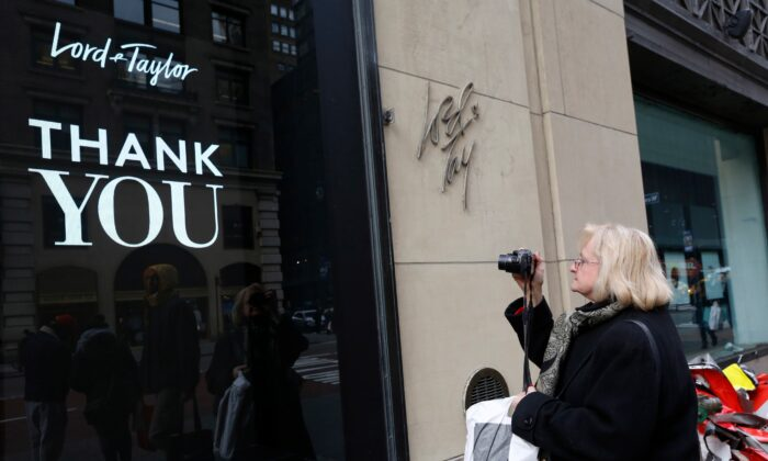 A woman, who declined to give her name, pauses to take a photo of a sign outside Lord & Taylor's flagship Fifth Avenue store in New York, N.Y., on Jan. 2, 2019. (Kathy Willens/AP Photo)