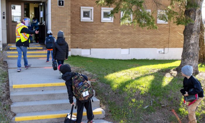 Students maintain social distancing as they enter Ecole Marie Rose in Saint Sauveur, Que., as elementary schools outside the greater Montreal area reopen on May 11, 2020. (The Canadian Press/Ryan Remiorz)
