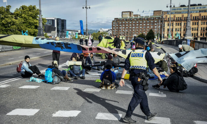 Climate change activists of Extinction Rebellion block the traffic at a bridge in central Stockholm on Aug. 28, 2020. (TT News Agency/Lars Schroder via Reuters)