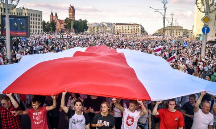 Belarus opposition supporters hold a giant former white-red-white flag of Belarus used in opposition to the government, during a demonstration in central Minsk on Aug. 16, 2020. (Sergei Gapon/AFP via Getty Images)