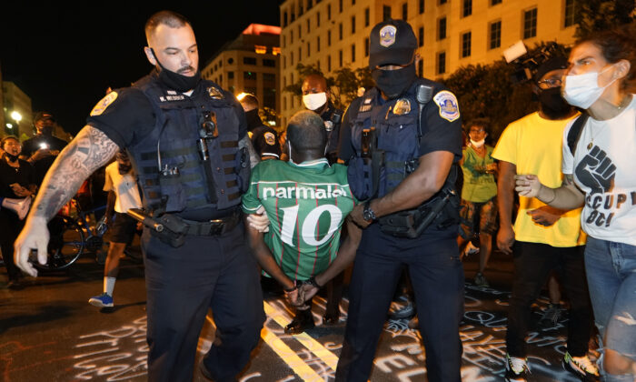 Police carry away a handcuffed protestor along a section of 16th Street, Northwest, renamed Black Lives Matter Plaza, in Washington, on Aug. 27, 2020. (Julio Cortez/AP Photo)