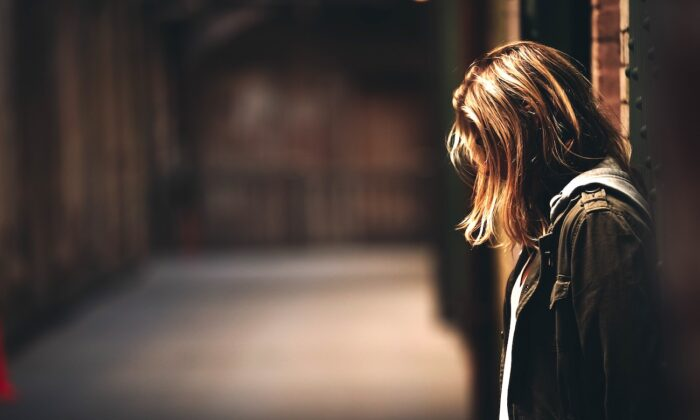 Stock photo of a girl standing in a dimly lit hallway. (Eric Ward/Unsplash)