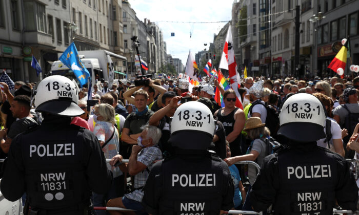 Police officers stand in front of demonstrators as they attend a rally against the government's restrictions following the CCP virus disease (COVID-19) outbreak, in Berlin, Aug. 29, 2020. (Christian Mang/Reuters)