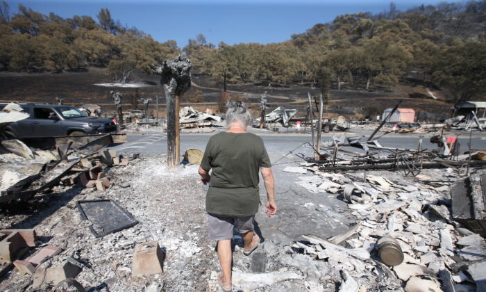 Artist Marcia Ritz, 77, leaves after looking through the rubble of her manufactured home at the Spanish Flat Mobile Villa trailer park in Lake Berryessa, Calif., on Aug. 27, 2020. (Jane Tyska/Bay Area News Group via AP)
