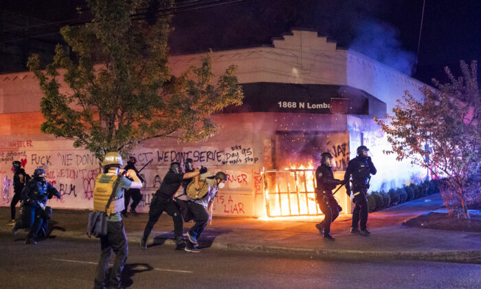 Portland police disperse a crowd after protesters set fire to the Portland Police Association (PPA) building early in the morning in Portland, Ore., on Aug. 29, 2020. (Nathan Howard/Getty Images)