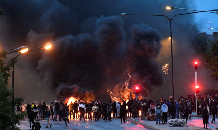 Smoke billows from the burning tyres, pallets, and fireworks during a riot in the Rosengard neighborhood of Malmo, Sweden on Aug. 28, 2020. (TT News Agency via Reuters)