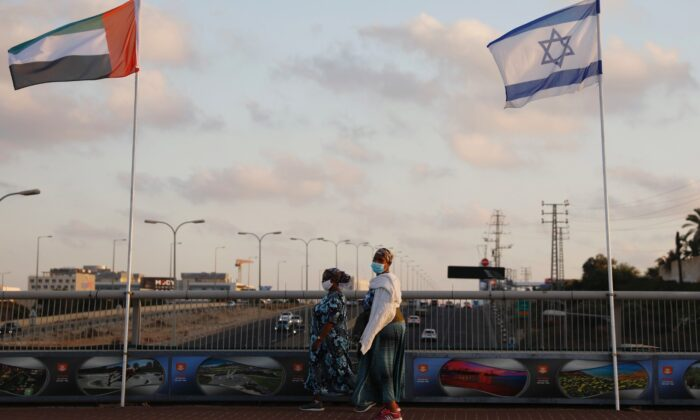 Women wearing face masks against the coronavirus walk past United Arab Emirates and Israeli flags at the Peace Bridge in Netanya, Israel, Sun., Aug. 16, 2020. (Ariel Schalit/AP Photo)