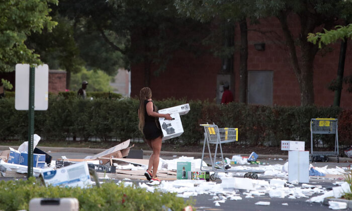 A person carries a box near a looted Best Buy store in Chicago, Ill., on Aug. 10, 2020. (Scott Olson/Getty Images)