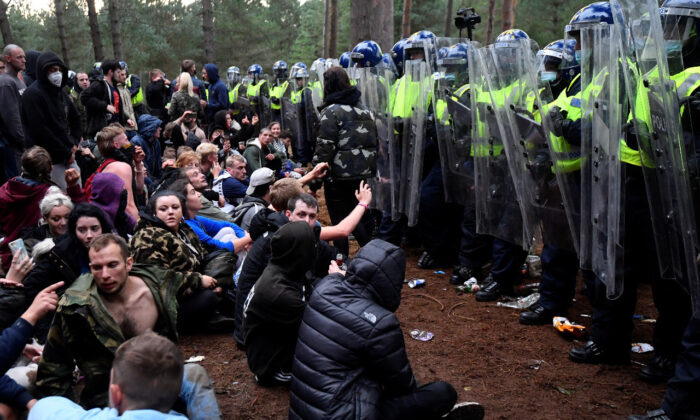 Revellers sit after police shut down a suspected illegal rave in Thetford Forest, in Norfolk, Britain on Aug. 30, 2020. (Reuters/Toby Melville)