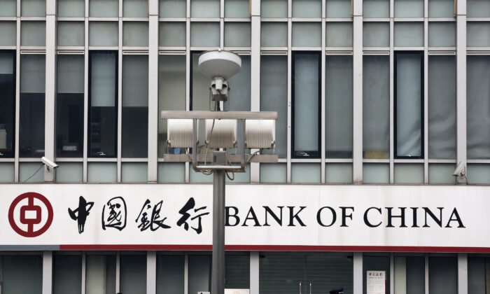 A security official and a man walk past a signboard of Bank of China at its branch in Beijing, on March 26, 2013. (Kim Kyung-Hoon/Reuters)