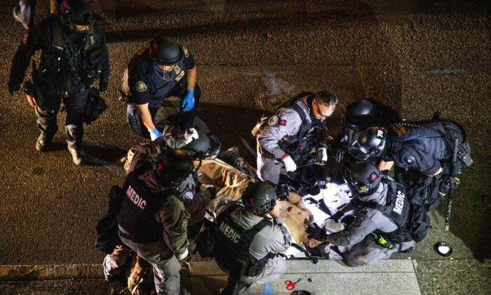 A man is treated after being shot in Portland, Ore., Aug. 29, 2020. The victim was later identified as Aaron Jay Danielson, who died from his wounds. Michael Reinoehl, an Antifa member, admitted to shooting Danielson. (Paula Bronstein/AP Photo)