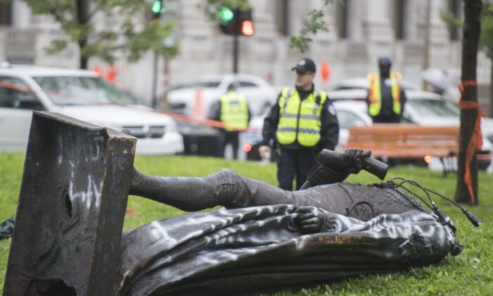 The statue of Sir John A. MacDonald lies headless on the grass after it was torn down following a demonstration in Montreal on Aug. 29, 2020. (Graham Hughes/The Canadian Press)