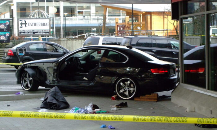 A black BMW sits crashed into the new CBC building after an apparent carjacking in Vancouver, Canada, on Dec. 29, 2009. (Ash Mishra/The Canadian Press)
