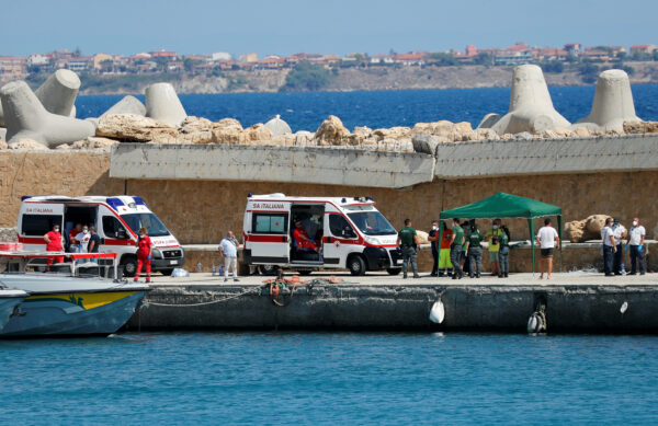 Emergency services are seen on the dock of Le Castella after a migrant boat caught fire during rescue operations off the coast of Crotone