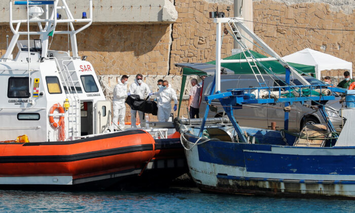 Emergency services carry a body at the dock of Le Castella after a migrant boat caught fire during rescue operations off the coast of Crotone, with some people still missing according to Italian media, Italy, on Aug. 30, 2020. (Remo Casilli/Reuters)