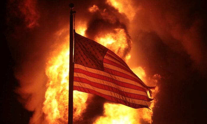 An American flag flies in front of a department of corrections building after it was set ablaze during a second night of rioting in Kenosha, Wis., on Aug. 24, 2020. (Scott Olson/Getty Images)