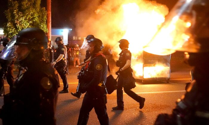 Portland police walk past a dumpster fire during a crowd dispersal in Portland, Ore., on Aug. 14, 2020. (Nathan Howard/Getty Images)