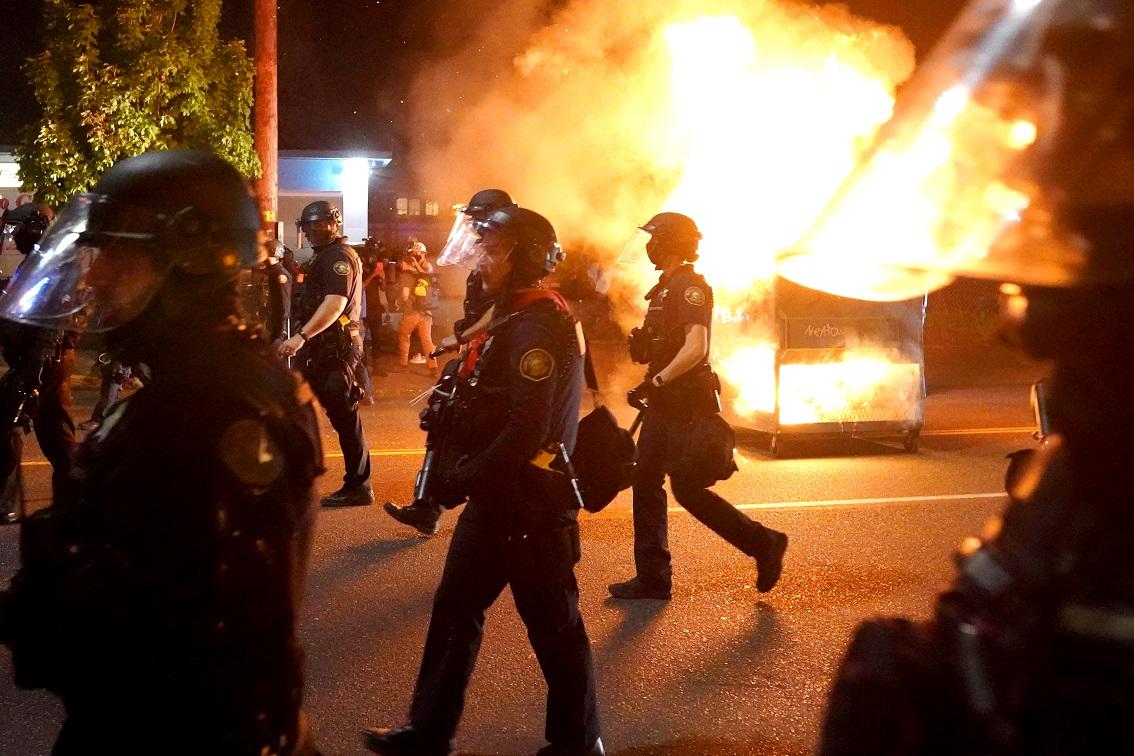 Portland police walk past a dumpster fire
