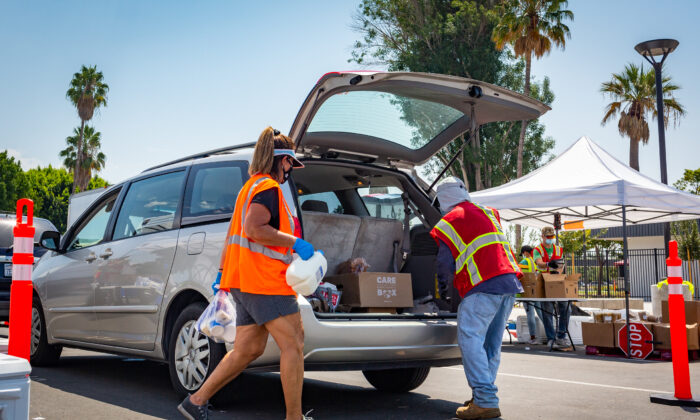Saddleback Church Food Pantry volunteers help load food items into the back of an SUV at Savanna High School in Anaheim, Calif., on Aug. 18, 2020. (John Fredricks/The Epoch Times)