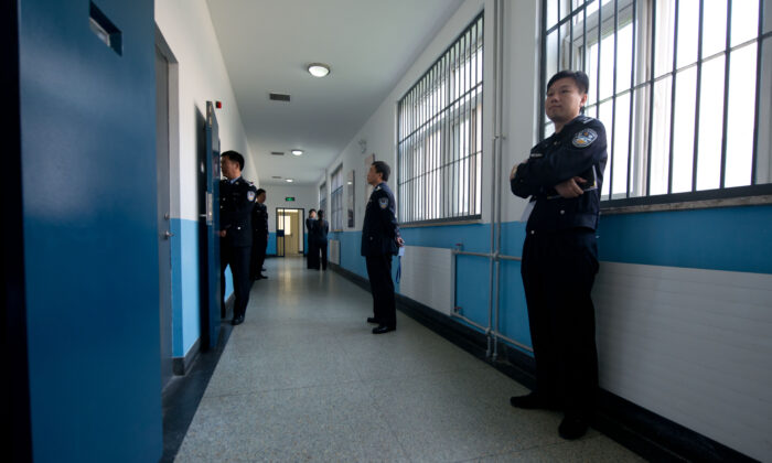 Police guards stand in a hallway inside the No.1 Detention Center during a government guided tour in Beijing on Oct. 25, 2012. (Ed Jones/AFP via Getty Images)