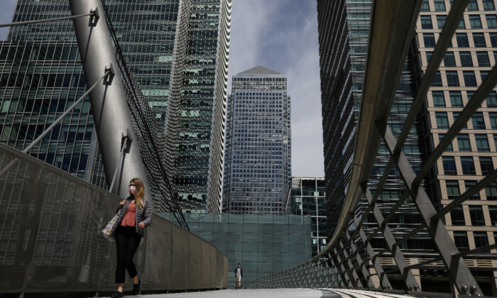 In this file photo a woman wearing a face mask crosses a bridge in front of One Canada Square in Canary Wharf following the outbreak of the CCP virus in London, on May 18, 2020. (Reuters/Simon Dawson)