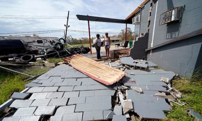 Monique Benjamin, left, and her 17-year old daughter Amiah Winbush look at the damage to their car detailing business, in Lake Charles, La., on Aug. 30, 2020. (Gerald Herbert/AP Photo)