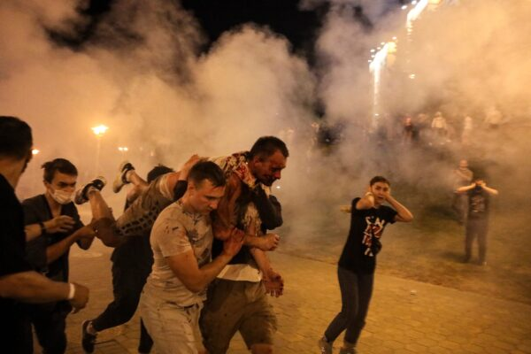 Protesters carry a wounded man during clashes with police