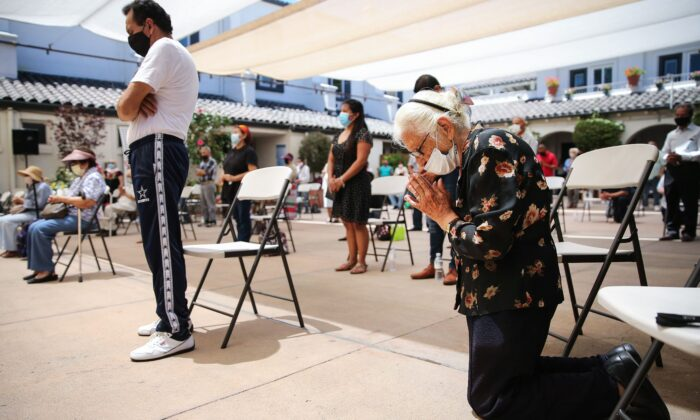 A worshipper kneels in prayer during Mass celebrated outdoors at the historic Our Lady Queen of Angels (La Placita) Church amid the COVID-19 pandemic in Los Angeles on Aug. 9, 2020. (Mario Tama/Getty Images)