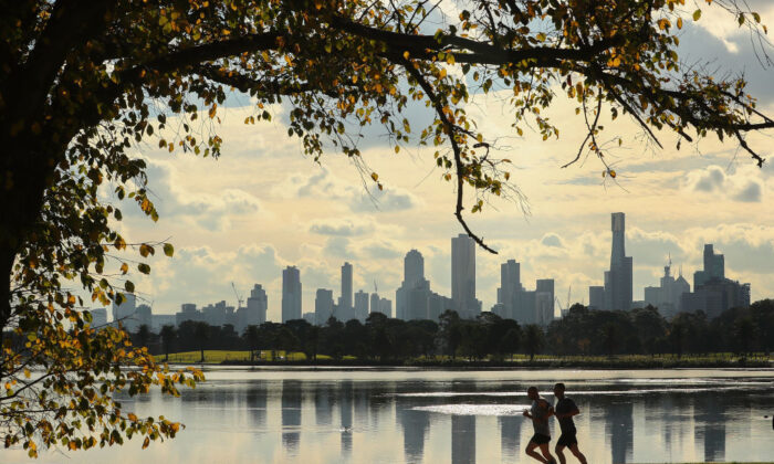 Two joggers run along Albert Park Lake on an Autumn day with  high-rise and apartment buildings in the city in the background on June 16, 2017 in Melbourne, Australia. (Scott Barbour/Getty Images)
