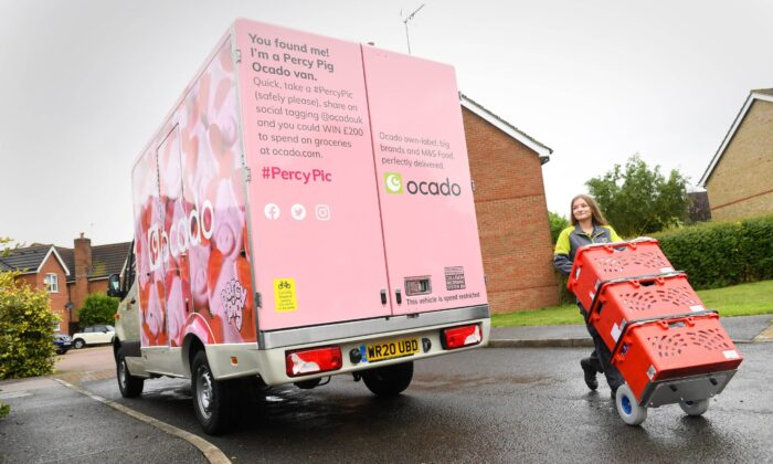 An Ocado delivery worker moves products beside one of the 10 Percy Pig branded Ocado vans, in Britain, on Sept. 1, 2020. (Doug Peters/PA Wire via Ocado)