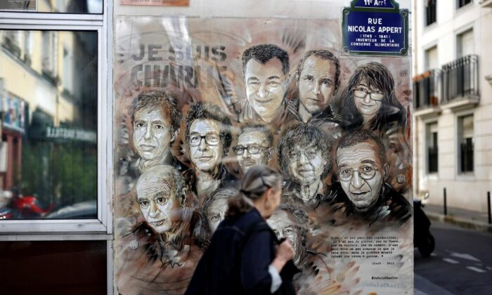 A woman walks past a painting by French street artist and painter Christian Guemy in tribute to members of Charlie Hebdo newspaper who were killed by jihadist gunmen in 2015, in Paris, on Aug. 31, 2020. (Thomas Coex/AFP via Getty Images)