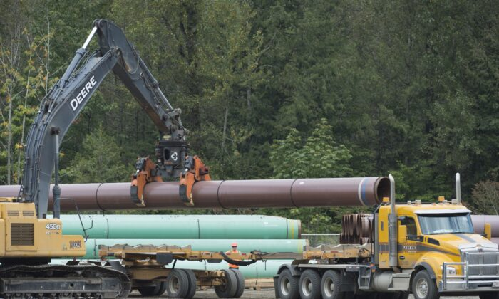 Pipeline pipes are loaded onto a truck at a Trans Mountain facility near Hope, B.C., on Aug. 22, 2019. (The Canadian Press/Jonathan Hayward)