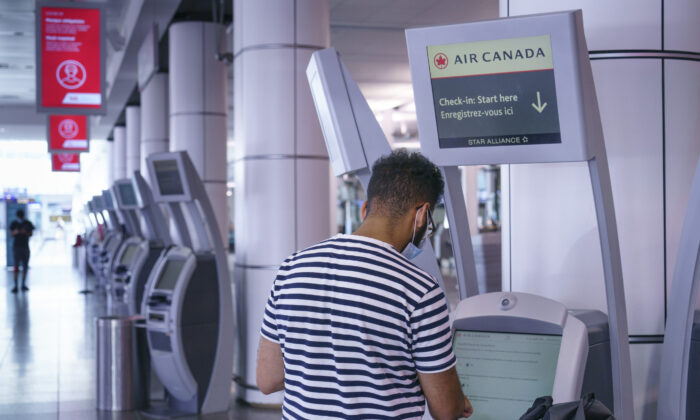 A passenger uses an Air Canada self service check-in kiosk at Montreal-Trudeau International Airport in Montreal on July 31, 2020. (The Canadian Press/Paul Chiasson)