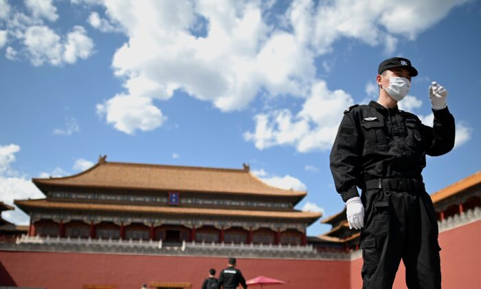 A security officer wearing a face mask stand guard in front of the entrance to the Forbidden City, while the closing of the Chinese Peoples Political Consultative Conference takes place in Beijing on May 27, 2020. (Noel Celis/AFP via Getty Images)