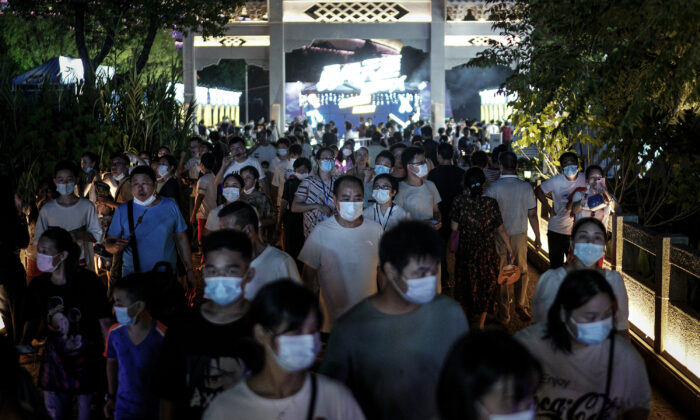 Residents wear masks while walking through the entrance of the Wuhan Beer Festival in Wuhan city, Hubei Province, China, on August 21, 2020. (Getty Images)
