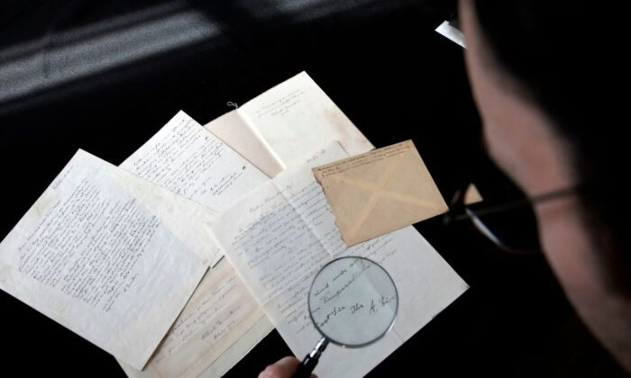 An employee uses a magnifying glass to inspect a series of letters by Nobel Prize-winning physicist Albert Einstein at Winner's auction house in Jerusalem, on March 6, 2018 prior to being auctioned later in the night with the rest of a series of nine. / AFP PHOTO / MENAHEM KAHANA        (Photo credit should read MENAHEM KAHANA/AFP via Getty Images)