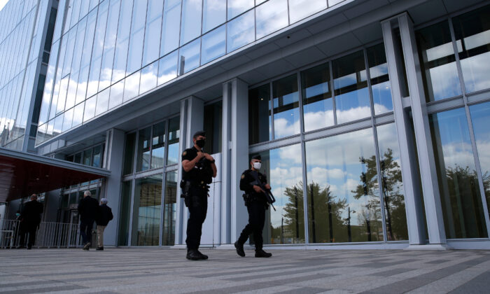 Police officers patrol outside the courthouse during the opening of the 2015 attacks trial in Paris on Sept. 2, 2020. (Francois Mori/AP Photo)