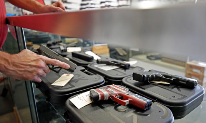 A worker restocks handguns at Davidson Defense in Orem, Utah, on March 20, 2020. (George Frey/AFP via Getty Images)