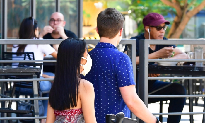 A pedestrian wears a face mask while walking past people dining outdoors in Los Angeles, California on August 25, 2020. (FREDERIC J. BROWN/AFP via Getty Images)