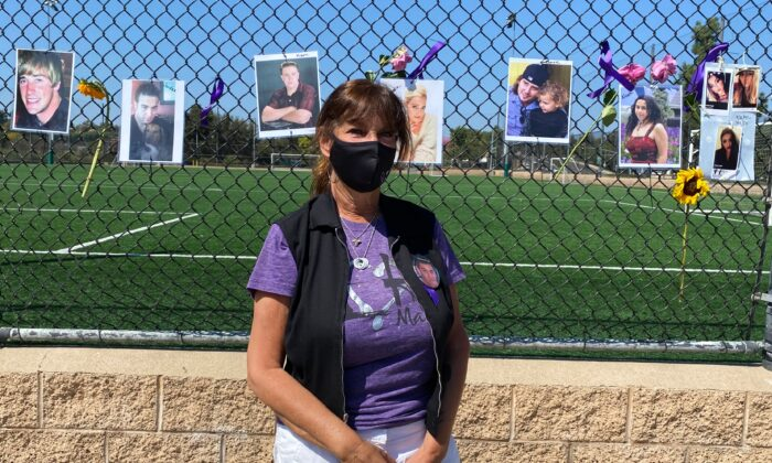 Event coordinator Jodi Barber stands in front of a chain-link fence lined with pictures of overdose victims on International Overdose Awareness Day at the Laguna Niguel Skate Park in Laguna Niguel, Calif., on Aug. 31, 2020. (Chris Karr/The Epoch Times)