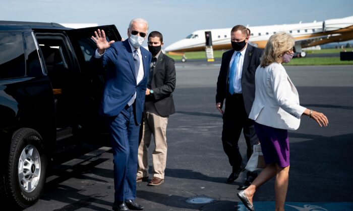 Democratic presidential candidate Joe Biden, with his wife Dr. Jill Biden (R), waves as he boards his plane in New Castle, Del., on Sept. 3, 2020. (Jim Watson / AFP via Getty Images)